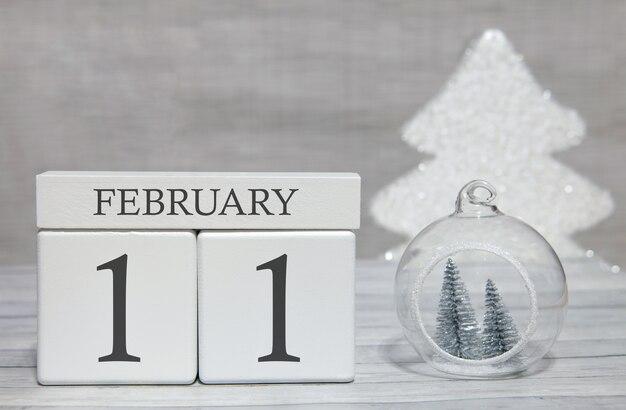 Calendario a forma di cubo per l'11 febbraio su superficie di legno e sfondo chiaro