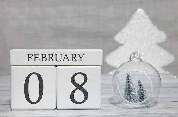 Calendario a forma di cubo per l'8 febbraio su superficie di legno e sfondo chiaro