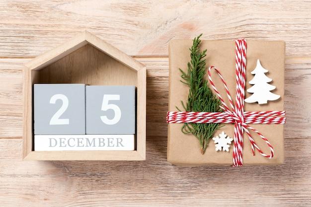 Calendario con data 25 dicembre e scatole regalo su colore, concetto di natale
