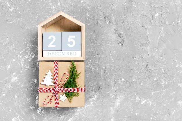 Calendario con data 25 dicembre e scatole regalo su colore