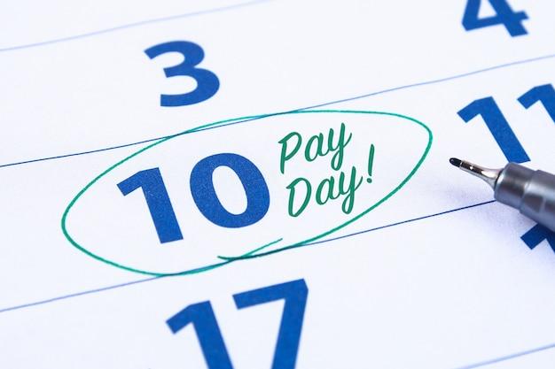 Calendario con il cerchio dell'indicatore nella parola giorno di paga