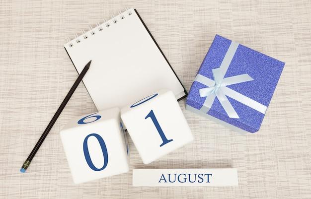 Calendario con testo blu e numeri alla moda per il 1 agosto e un regalo in una scatola.
