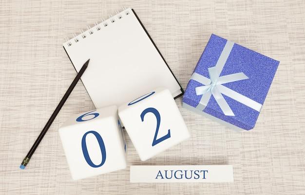 Calendario con testo blu e numeri alla moda per il 2 agosto e un regalo in una scatola.