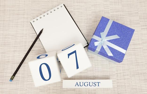 Calendario con testo blu e numeri alla moda per il 7 agosto e un regalo in una scatola.