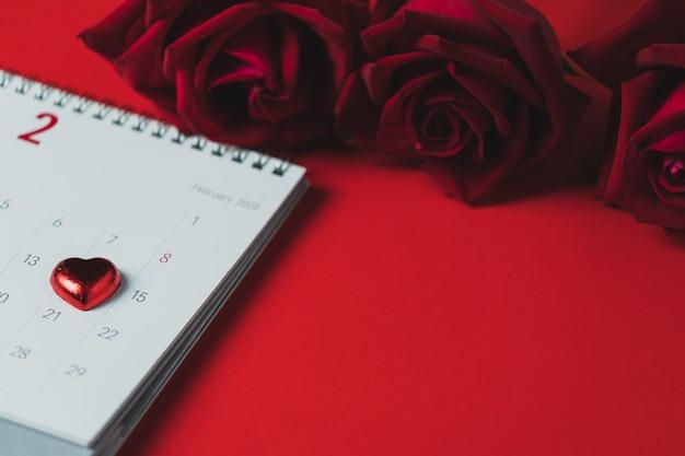Calendario del libro bianco e rosa rossa disposti su una tavola rossa, su una vista superiore e sullo spazio della copia, tema di san valentino