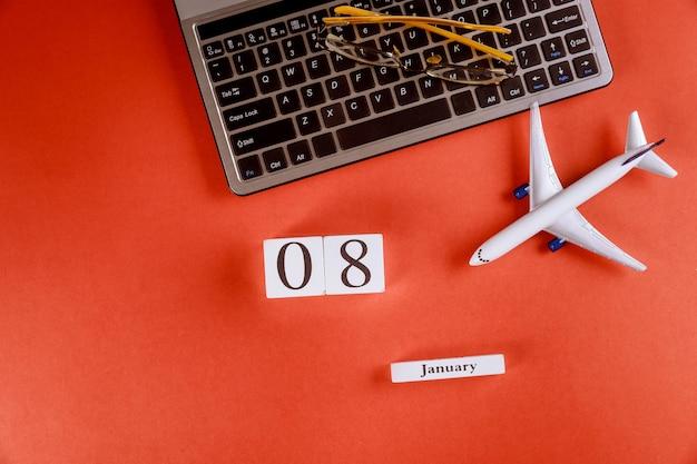 Calendario dell'8 gennaio con gli accessori sulla scrivania dell'area di lavoro di affari sulla tastiera di computer, aeroplano, fondo rosso di vetro