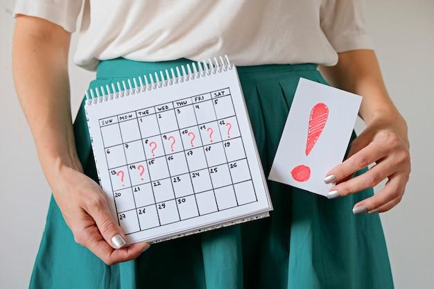 Calendario della tenuta della donna con il periodo e il punto esclamativo segnati mancati. gravidanza indesiderata e ritardo nelle mestruazioni.