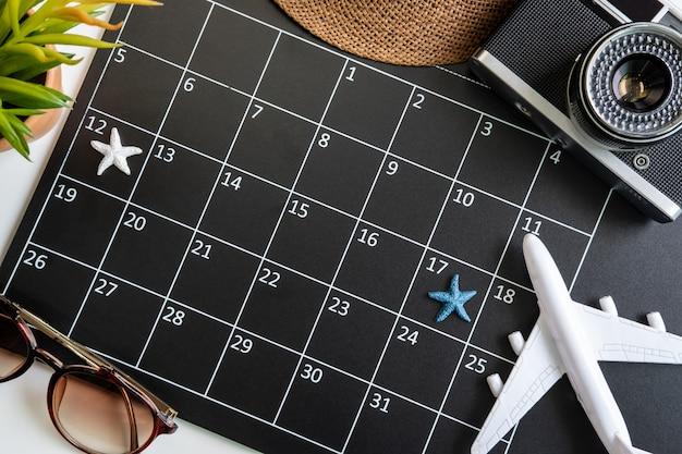 Calendario delle vacanze con fotocamera e articoli da viaggio, vista dall'alto