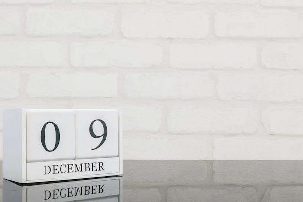 Calendario di legno bianco del primo piano con la parola nera di 9 dicembre sulla tavola di vetro nera e sul muro di mattoni bianco