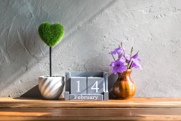 Calendario di legno d'annata per il 14 febbraio con cuore verde sull'amore di legno della tavola e sul fondo di concetto di san valentino, contesto.