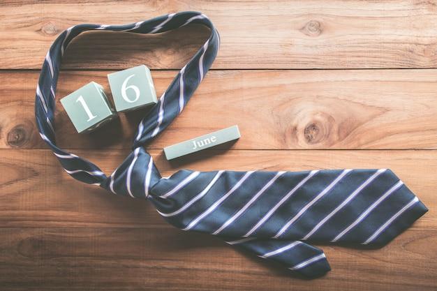 Calendario di legno d'annata per il 16 giugno con il concetto del fondo dell'iscrizione di festa del papà felice della cravatta.