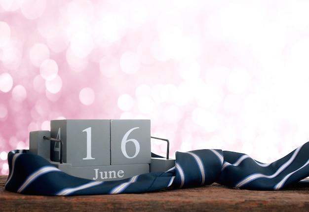 Calendario di legno d'annata per il 16 giugno con la cravatta fondo dell'iscrizione di festa del papà felice.
