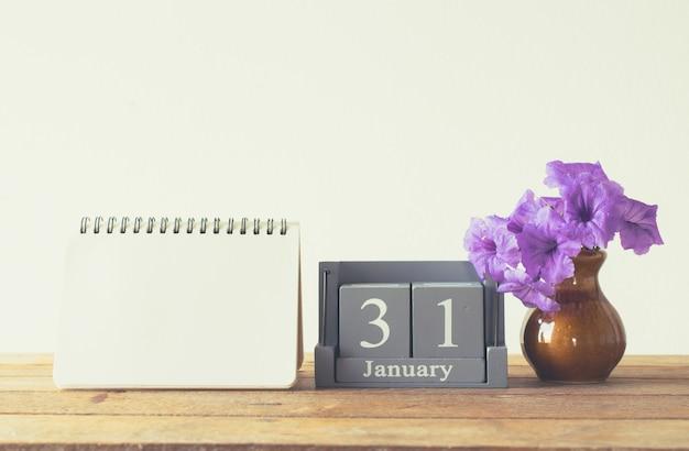 Calendario di legno d'annata per il giorno 31 gennaio sulla tavola di legno con il taccuino vuoto