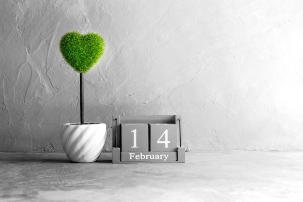 Calendario di legno dell'annata per il 14 febbraio con cuore verde sul tavolo di legno