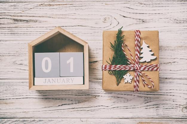 Calendario di natale 1 gennaio. regalo di natale, rami di abete su vintage, tonica in legno. copia spazio, vista dall'alto