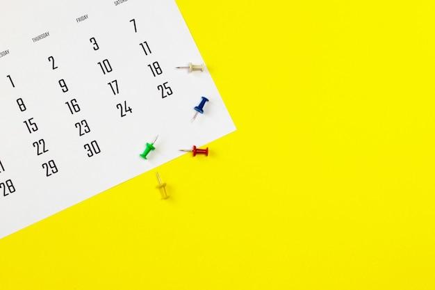 Calendario e puntine da disegno su sfondo giallo