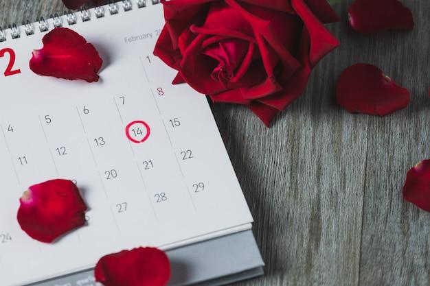 Calendario e rose rosse del libro bianco disposti su un pavimento di legno grigio, su una vista superiore e sullo spazio della copia, tema di san valentino