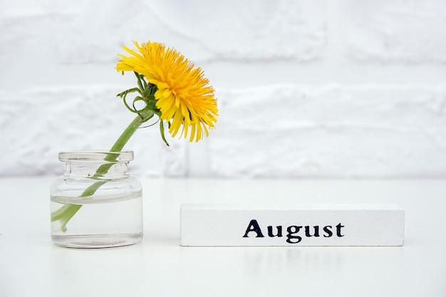 Calendario estivo in legno mese di agosto e dente di leone giallo in vaso bottiglia sul tavolo