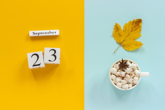 Calendario in legno 23 settembre, tazza di cacao con marshmallow e foglie di autunno gialli su sfondo blu giallo.