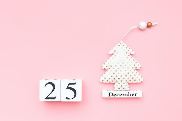 Calendario in legno 25 dicembre, albero di natale in tessuto su sfondo rosa. concetto di buon natale.