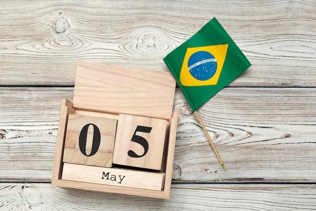 Calendario in legno a forma di cubo per il 5 maggio su fondo di legno