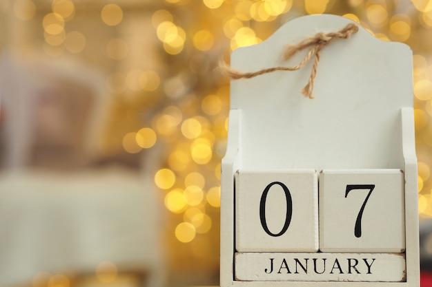 Calendario in legno bianco con cubi e data 07 gennaio e luci bokeh da una ghirlanda in background.