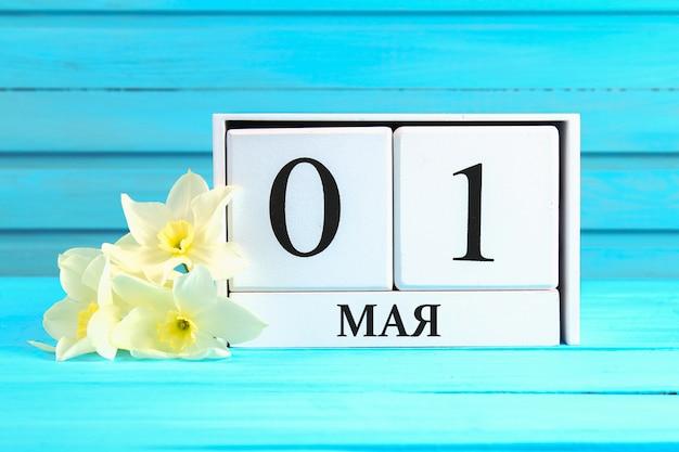 Calendario in legno bianco con il testo in russo: 1 maggio. festa dei lavoratori e primavera.