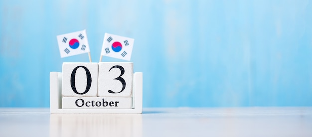 Calendario in legno del 3 ottobre con bandiere della repubblica di corea in miniatura.