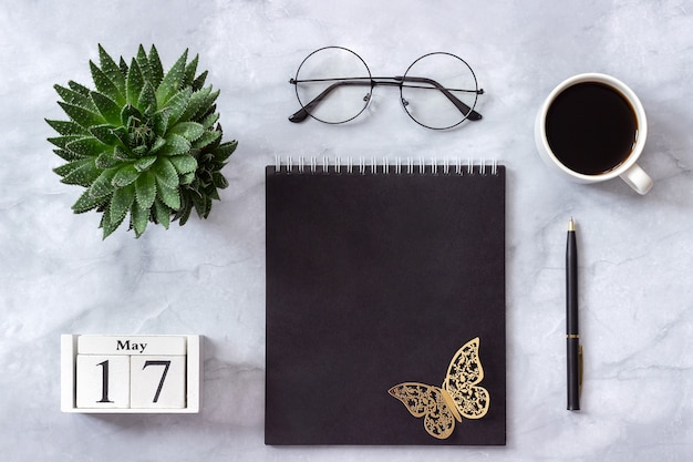 Calendario maggio 17. blocco note nero, tazza di caffè, succulenta, bicchieri su marmo