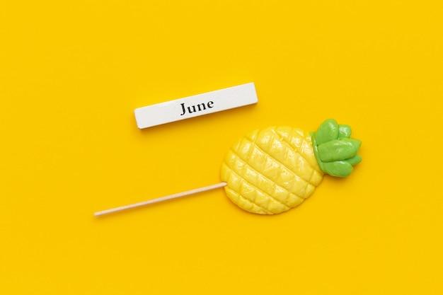 Calendario mese estivo giugno, lecca-lecca di ananas su sfondo giallo.
