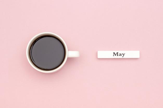 Calendario mese maggio e tazza di caffè nero su sfondo di carta rosa pastello.