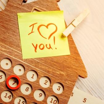 Calendario perpetuo in legno a forma di una casa su un tavolo di legno con una nota allegata