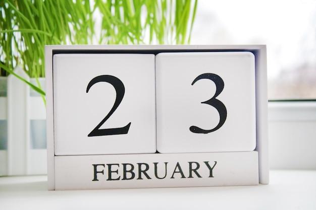Calendario perpetuo in legno bianco con la data del 23 febbraio alla finestra.