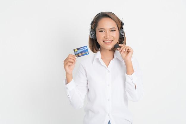 Call center della donna con la tenuta della cuffia avricolare e la carta di credito.