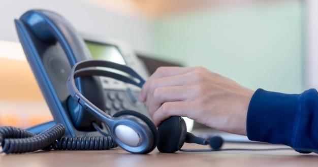 Call center dipendente man mano che tiene la cuffia sul telefono