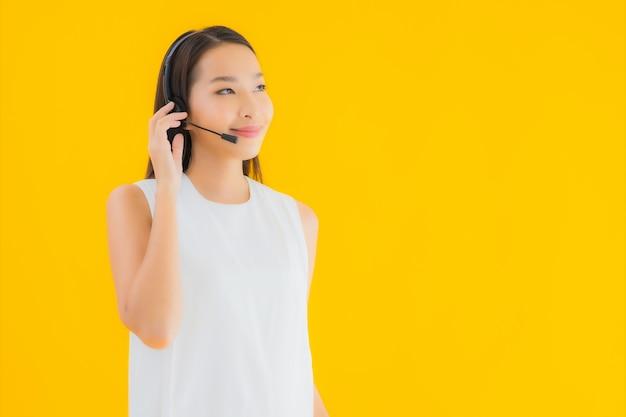 Callcenter della bella giovane donna asiatica del ritratto per l'assistenza
