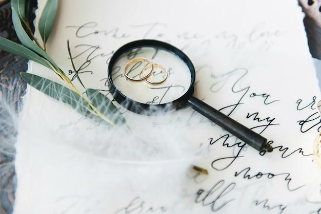 Calligrafia e decorazioni per matrimoni. ispirazione. partecipazioni di nozze, buste, cartoline, stampa, lente d'ingrandimento, anelli. messa a fuoco selettiva