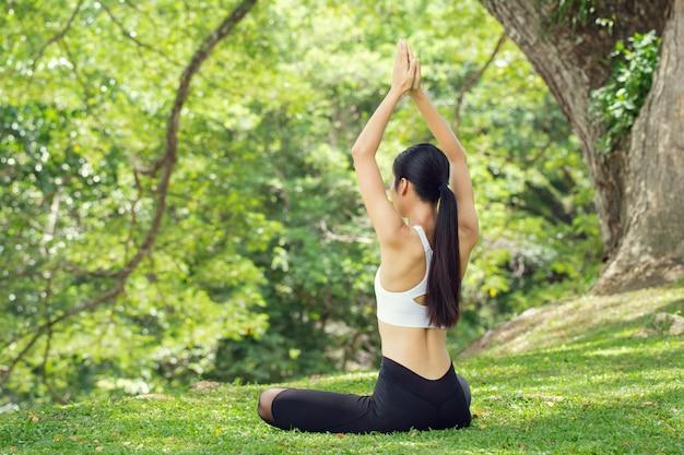Calma e relax.healthy donna yoga stile di vita equilibrato praticando meditazione ed energia zen esercizio sport yoga all'aperto. concetto di vita sana.