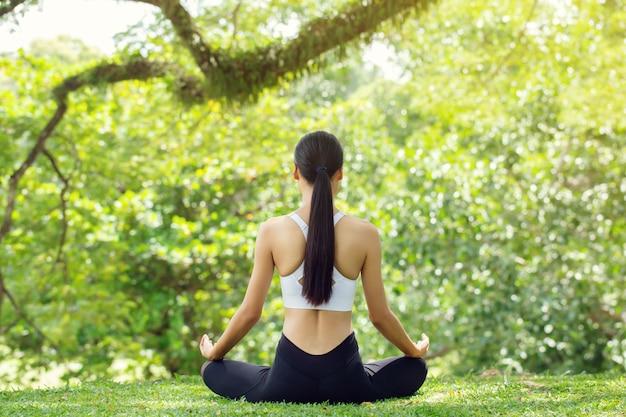 Calma e relax, le donne asiatiche meditano mentre praticano lo yoga nel parco all'aperto. concetto di libertà felicità della donna. immagine tonica vita sana