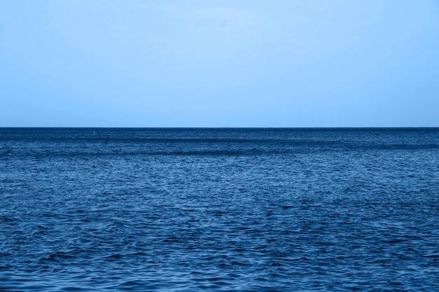 Calma mare blu onde superficie morbida oceano e cielo blu in classico colore blu alla moda