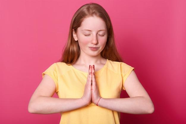Calma ragazza adolescente caucasica sta isolata sul rosa mentre prega, tiene gli occhi chiusi, chiede a dio qualcosa di importante per lei, indossa una maglietta casual gialla.