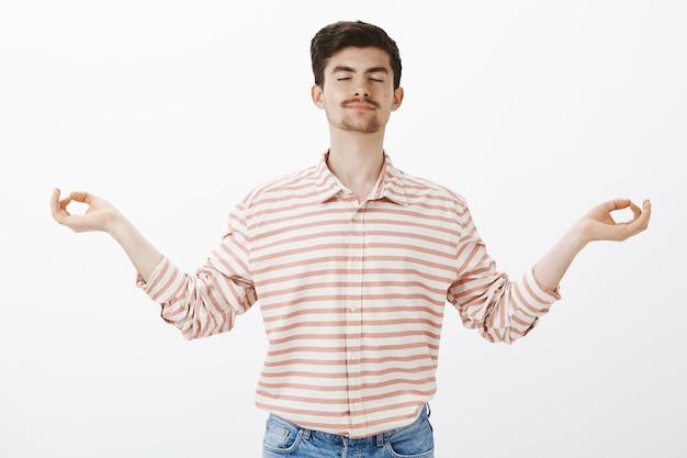 Calmarsi, inalare energia positiva. bel ragazzo caucasico spensierato con barba e baffi, chiudendo gli occhi e sorridendo, allargando le mani con gesto zen, meditando o praticando yoga