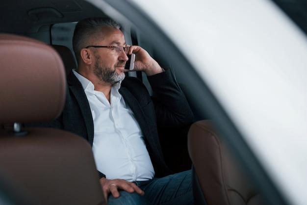 Calmo e buon umore. avere una chiamata di lavoro mentre era seduto sul retro di un'auto di lusso moderna. uomo anziano con gli occhiali e abbigliamento ufficiale