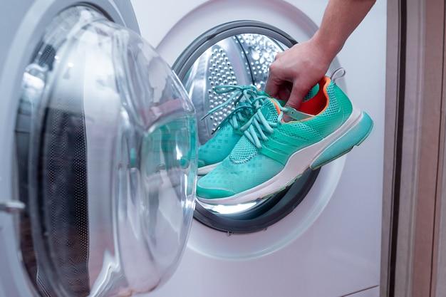 Calzature sporche della lavanderia in una lavatrice a casa. cura delle scarpe