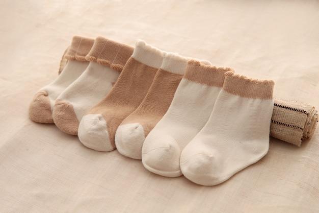 Calzini del bambino che appendono sulla corda da bucato su fondo di legno