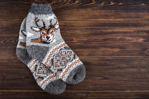 Calzini lavorati a maglia invernali con cervi su legno.