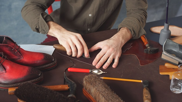 Calzolaio attraente impegnato nel processo di fabbricazione di scarpe