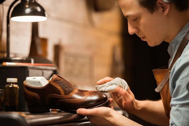 Calzolaio concentrato in officina che produce scarpe