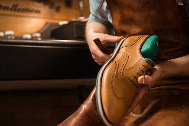 Calzolaio in officina che produce scarpe