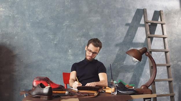 Calzolaio serio con gli occhiali che fa una brutta copia per riparare le scarpe